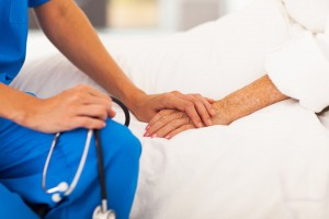 Nurse holds elderly patient's hand